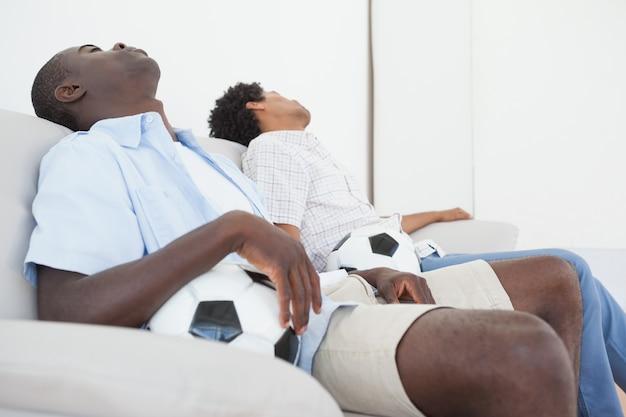 Umgekippte fußballfans, die zurück auf couch sitzen