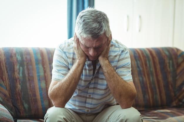 Umgekippter älterer mann, der im wohnzimmer sitzt