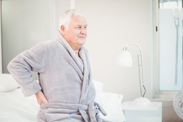 Umgekippter älterer mann, der mit rückenschmerzen auf bett sitzt