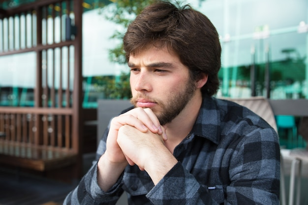 Umgekippter junger mann, der über schlechte nachrichten denkt