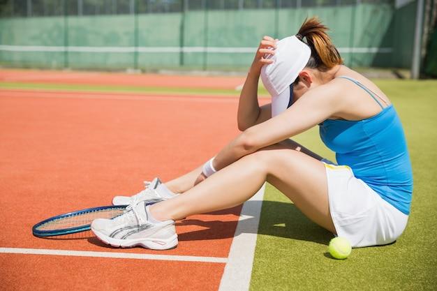 Umgekippter tennisspieler, der auf gericht sitzt
