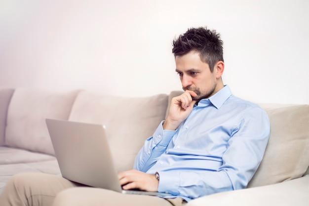 Umgekippter und besorgter junger geschäftsmann, der am laptop sitzt und arbeitet