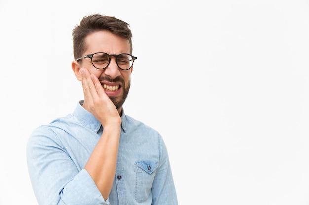 Umgekippter unglücklicher kerl, der backe mit schmerzgesicht hält