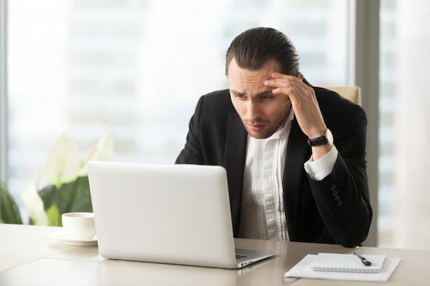 Umgekippter verwirrter geschäftsmann, der laptopbildschirm betrachtet