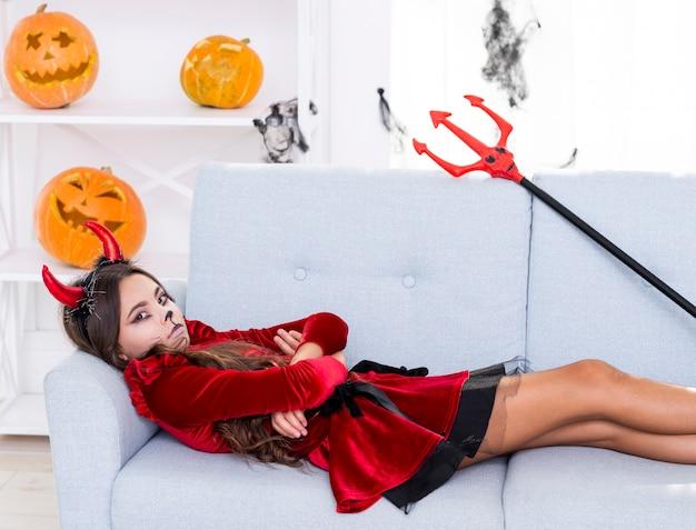 Umgekipptes junges mädchen, das auf einem sofa sitzt
