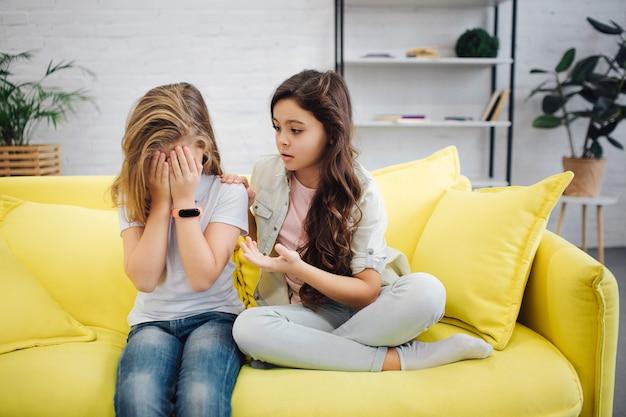 Umgekipptes mädchen auf linkem fellgesicht mit den händen. sie weint. jugendlicher sitzen mit ihrer freundin auf gelbem sofa im raum. brünette versuchen, sie zu trösten.