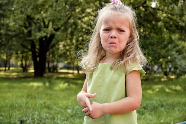 Umgekipptes mädchenkind, das im park schreit. elternschaft, kinderpsychologie.