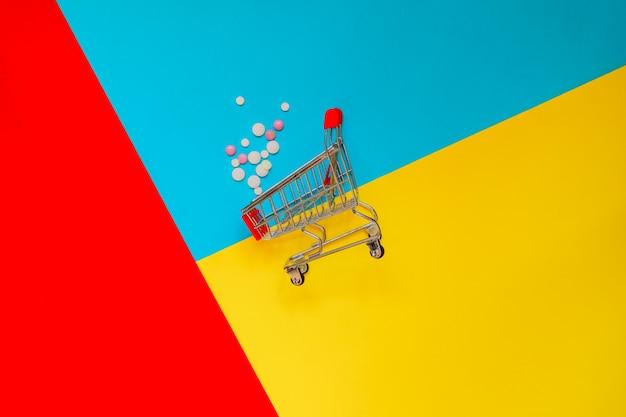 Umgestürzter einkaufswagen und verstreute medizinpillen an mehrfarbiger wand. konzept der medizin-, gesundheits- und apothekenindustrie.