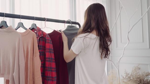 Umkleideraum der hauptgarderobe oder des kleidungsgeschäfts. asiatische junge frau, die ihre modeausstattungskleidung wählt