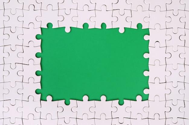 Umrahmung in form eines rechtecks aus weißem puzzle rund um die grüne fläche