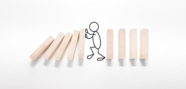Umriss einer person, die den domino-effekt auf weißem hintergrund stoppt. das konzept der zuverlässigkeit, professionalität und effizienz.