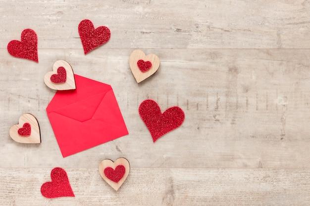 Umschlag für valentinsgrüße mit herzen auf hölzernem hintergrund