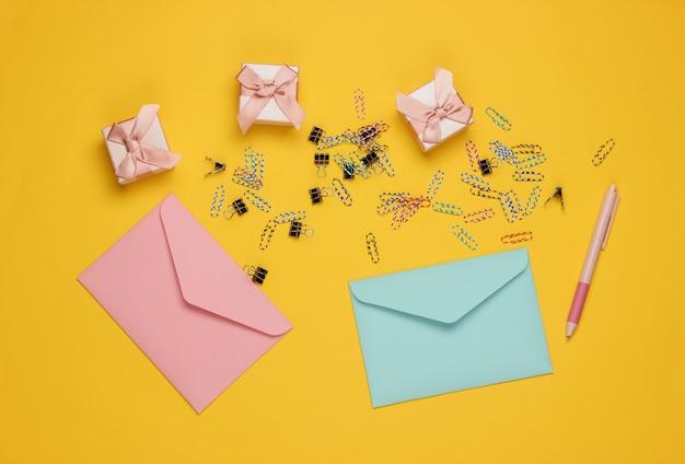Umschlag, geschenkboxen und büroklammern auf gelbem hintergrund. draufsicht