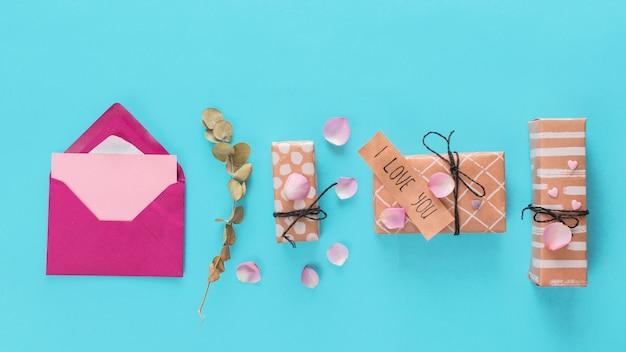 Umschlag in der nähe von geschenkkartons mit anhänger, pflanzen und blütenblättern