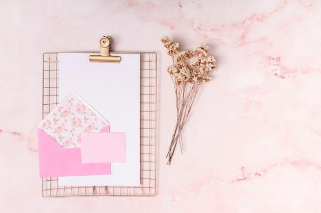 Umschlag in der nähe von papieren und pflanzen
