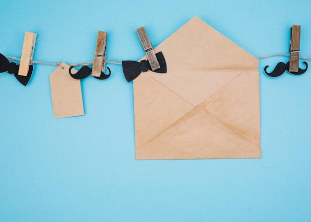 Umschlag in der nähe von tag, dekorativen fliege und schnurrbart am faden