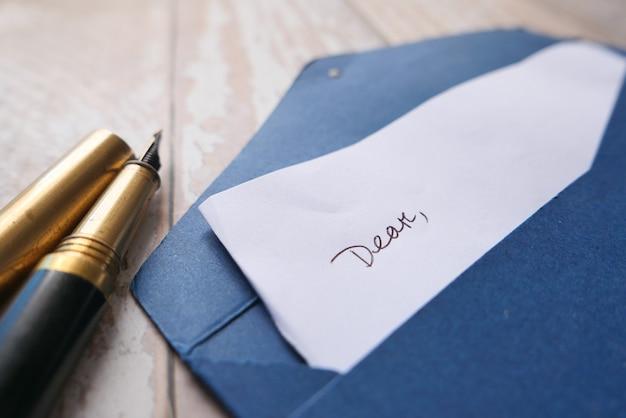 Umschlag, leeres papier und füllfederhalter auf dem tisch