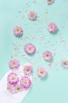 Umschlag mit blumen und blütenblättern auf einem pastellhintergrund