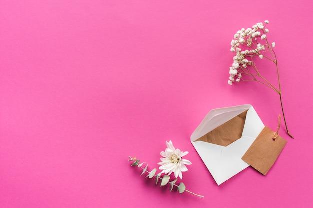 Umschlag mit blumenniederlassungen auf rosa tabelle
