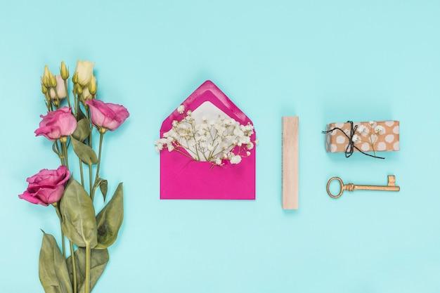 Umschlag mit blumenniederlassungen und rosa rosen