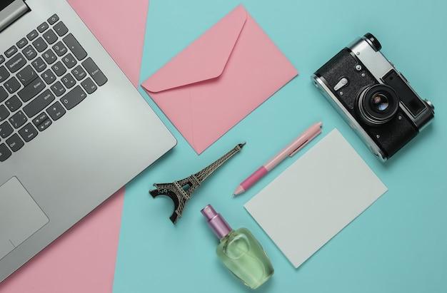 Umschlag mit brief, retro-kamera, laptop und schönheitszubehör auf rosa blauem pastellhintergrund. draufsicht. reisekonzept. flach liegen