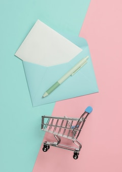 Umschlag mit brief und einkaufswagen auf rosa blauem pastellhintergrund. modell für valentinstag, hochzeit oder geburtstag. draufsicht