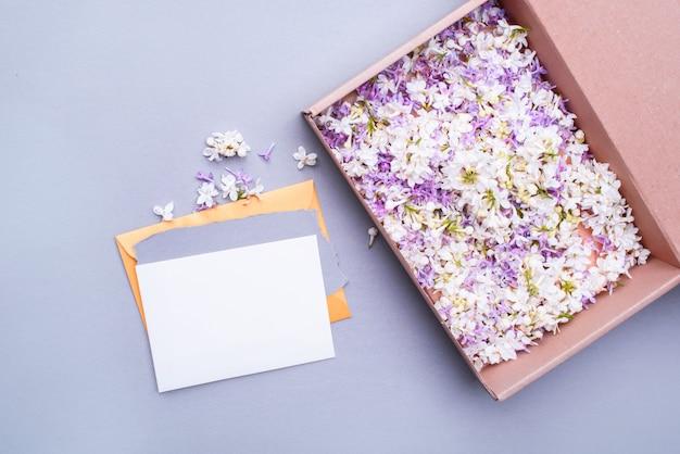 Umschlag mit einem leeren brief mit einem geschenk, lila blumen. urlaubsinhalt.