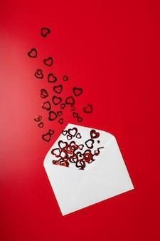 Umschlag mit herzen auf rotem grund