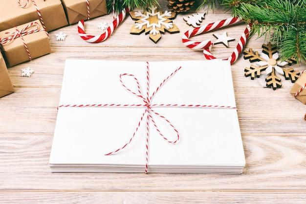 Umschlag mit leerem blatt papier auf weihnachten - tannenzweig, tannenzapfen, rotes band, stern und herz von bonbons.