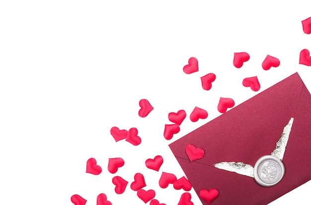 Umschlag mit liebesbrief und rotem herzformkonfetti. valentinstag, flachgelegt, draufsicht