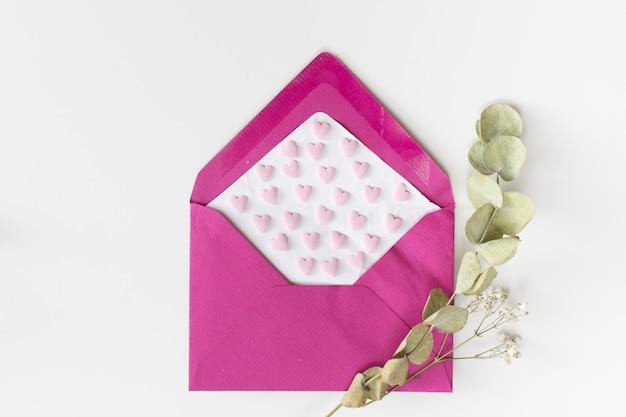 Umschlag mit papier mit ornamentherzen in der nähe von werkszweigen