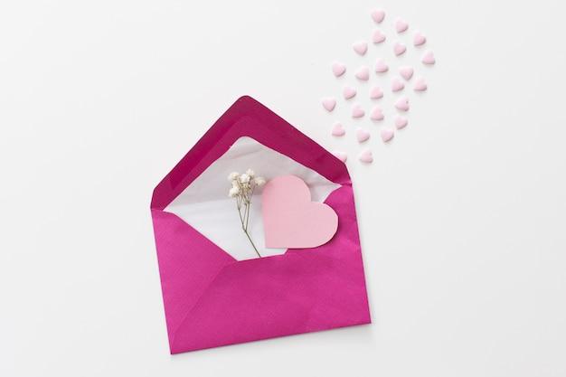 Umschlag mit papierherz und pflanzenzweig