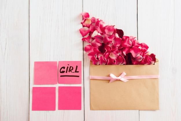 Umschlag mit rosenblättern und rosa aufklebern mit textmädchen