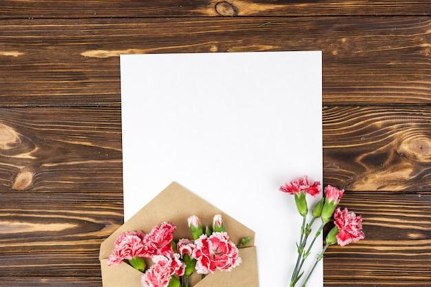 Umschlag mit roten gartennelkenblumen und leerem weißbuch über holzoberfläche