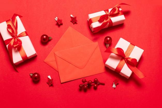 Umschlag mit zwei rottönen mit weihnachtsdekor, geschenkkästen auf einem roten hintergrund