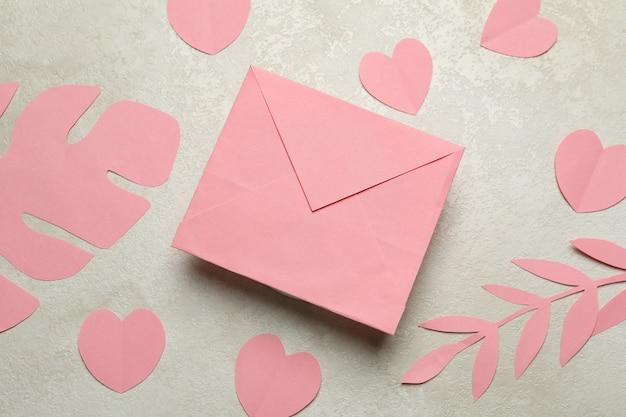 Umschlag, papierblätter und herzen auf weißem strukturiertem hintergrund