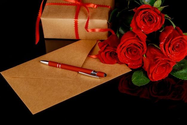 Umschlag, stift und strauß roter rosen auf schwarzem tisch. valentinstag konzept.