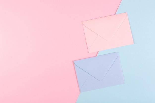 Umschlagzusammensetzung des blauen papiers auf rosa hintergrund.