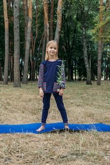 Umweltbildung für kinder kleines mädchen, das junge pflanze in den händen gegen grünen baum hält