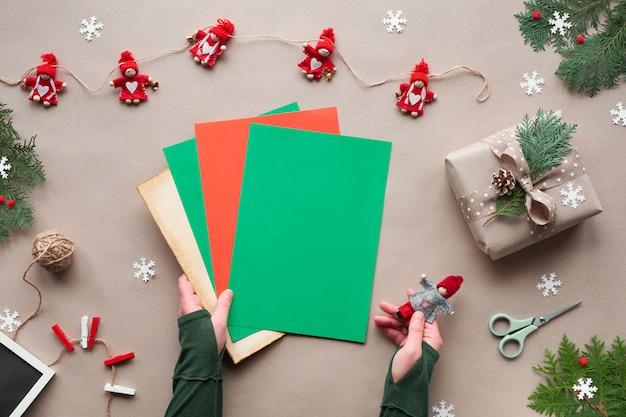 Umweltfreundliche alternative weihnachten. null abfall weihnachten, flache lage, draufsicht auf bastelpapier textilpuppe girlande, stern, hände halten farbpapier mit kopierraum, für ihren text oder schriftzug.