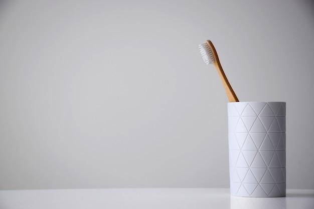 Umweltfreundliche bambuszahnbürste im weißen halter