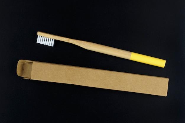 Umweltfreundliche bambuszahnbürste in der papierverpackung auf schwarzem