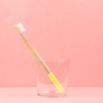 Umweltfreundliche bambuszahnbürste in einem transparenten glas auf koralle
