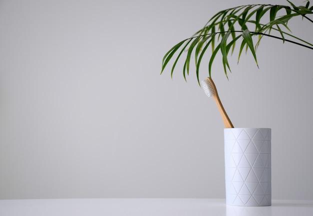 Umweltfreundliche bambuszahnbürste in weißem halter und palmblatt