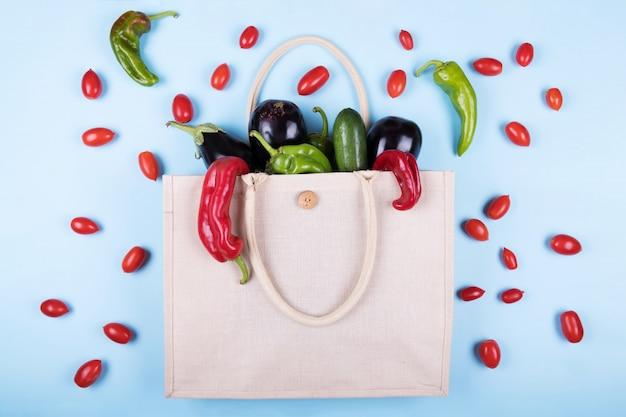 Umweltfreundliche baumwolltasche mit gemüse: auberginen, hässliche paprikaschoten, tomaten, zucchini auf pastellblauem, minimalem naturstil