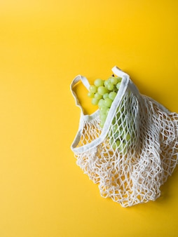 Umweltfreundliche beige einkaufstasche mit trauben auf gelbem hintergrund.