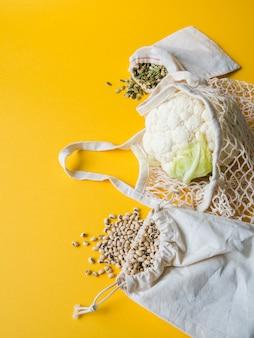Umweltfreundliche beige einkaufstaschen mit blumenkohl, bohnen, kürbiskerne auf gelbem hintergrund