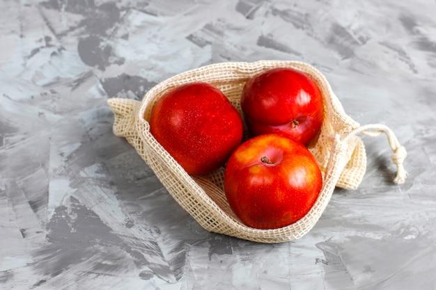 Umweltfreundliche, einfache einkaufstaschen aus beiger baumwolle zum kauf von obst und gemüse mit sommerfrüchten.