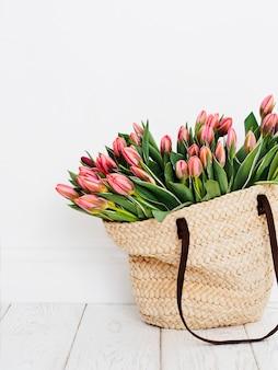 Umweltfreundliche einkaufstasche mit tulpen vor einem weißen wandhintergrund gewebt