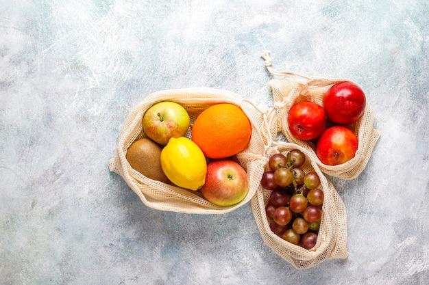 Umweltfreundliche einkaufstaschen aus einfacher beige baumwolle für den kauf von obst und gemüse mit sommerfrüchten.